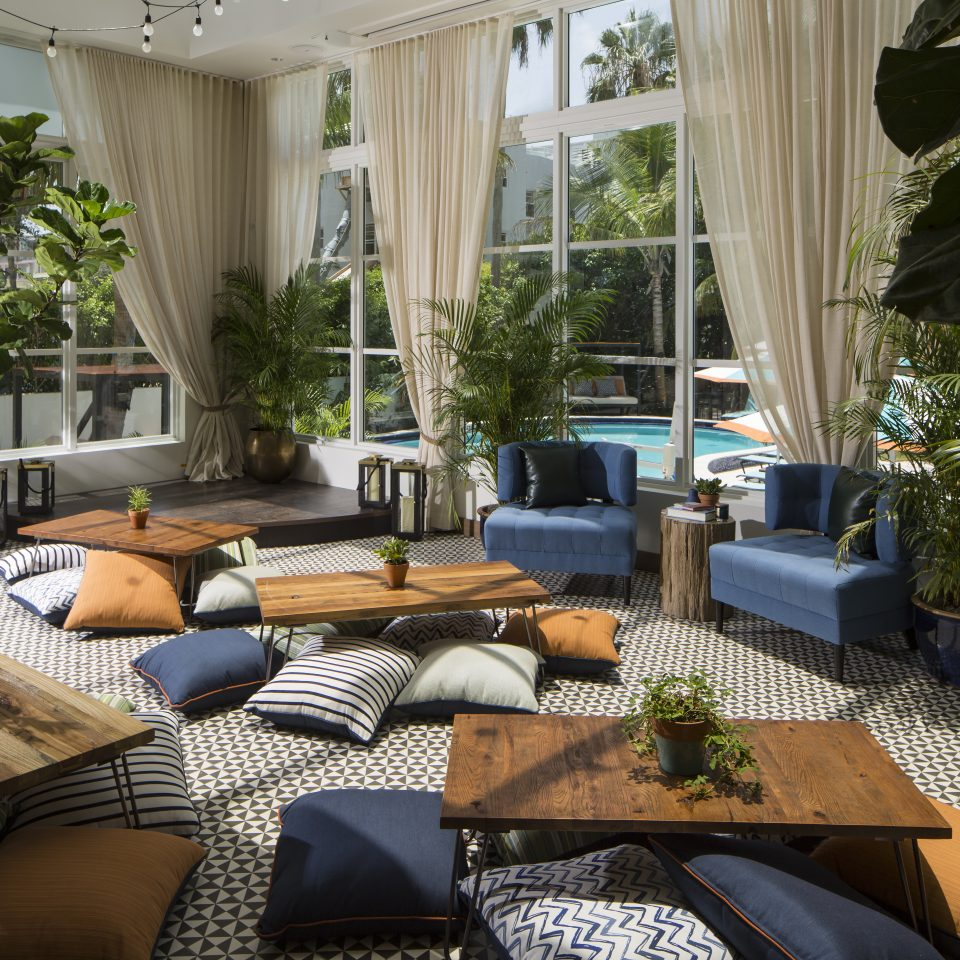 Cozy communal space with pillows on the floor for seating and low to the ground coffee tables overlooking an outdoor pool