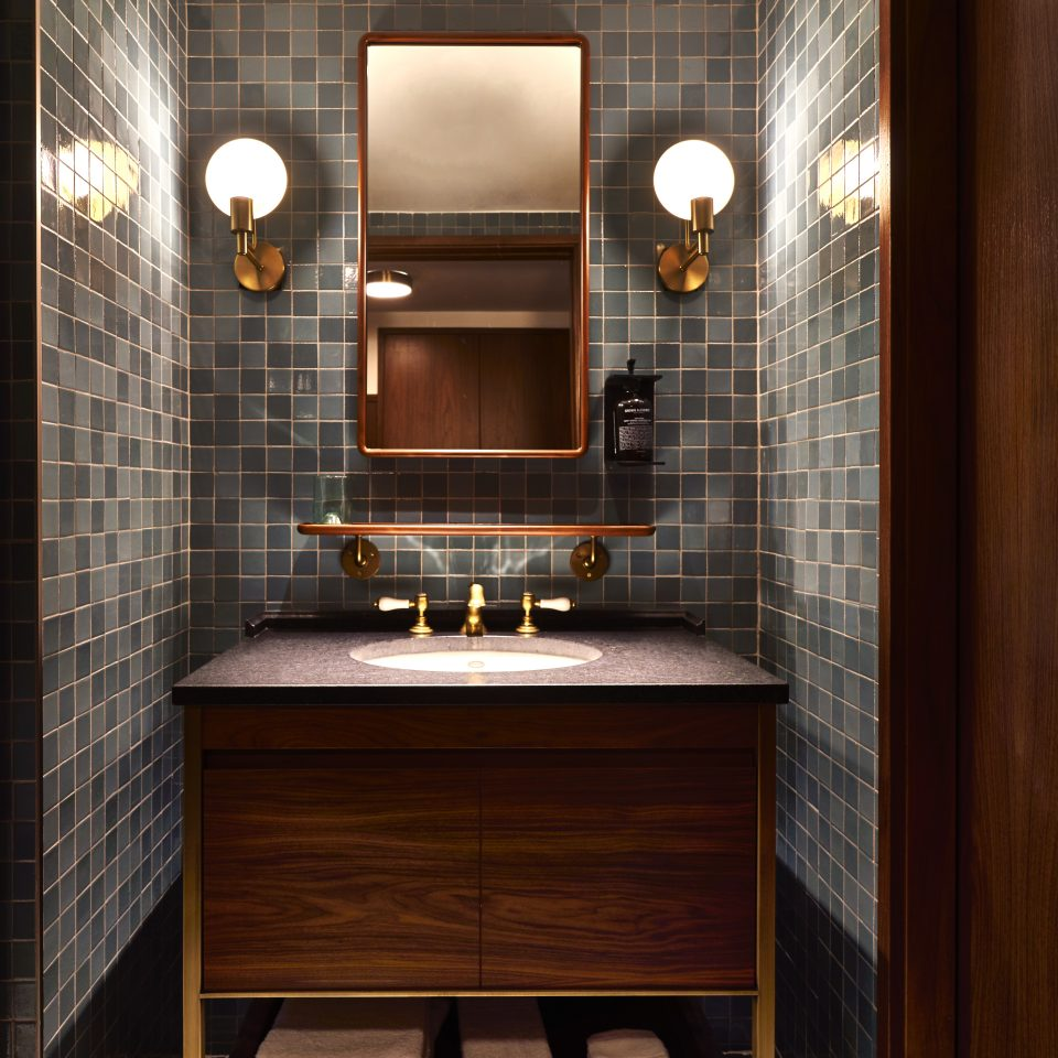 Frontal of large wooden sink in blue tiled bathroom