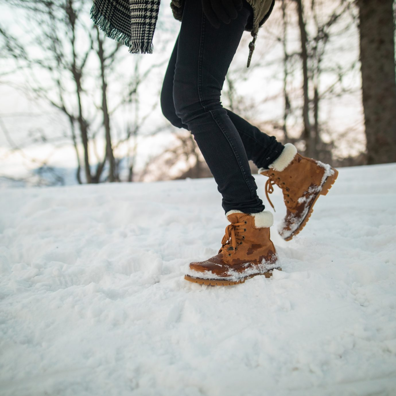 woman hiking in the mountains on a snowy day, best winter boots