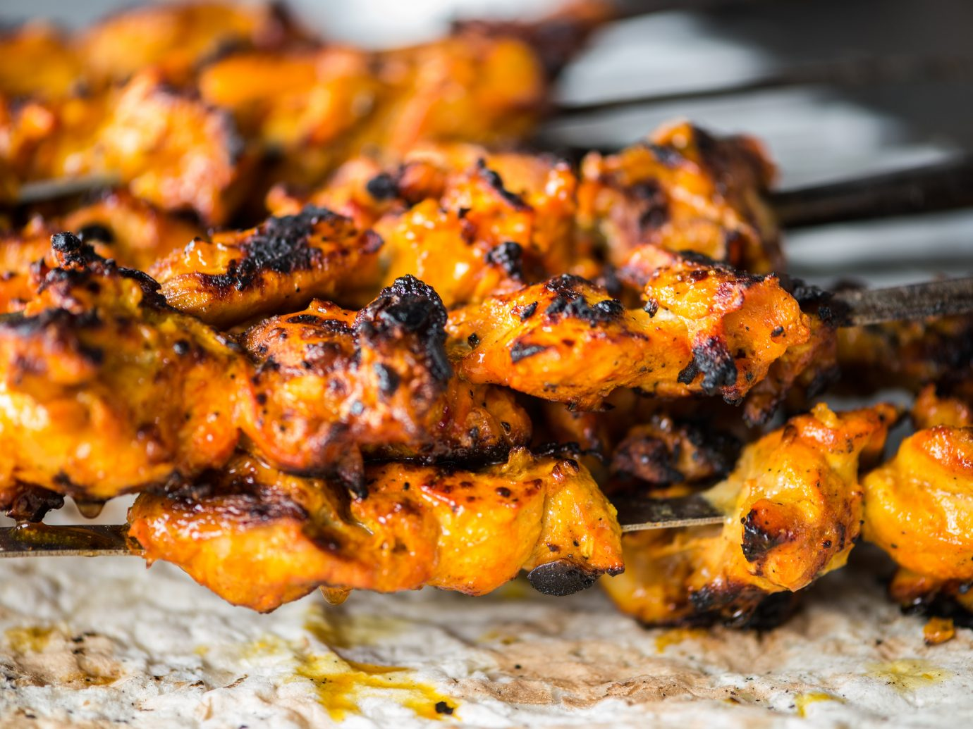 Closeup of freshly grilled chicken tikka masala kebabs on skewers dripping onto a piece of naan flatbread cooked in a Tandoori oven. Dubai, UAE, Middle East, GCC.