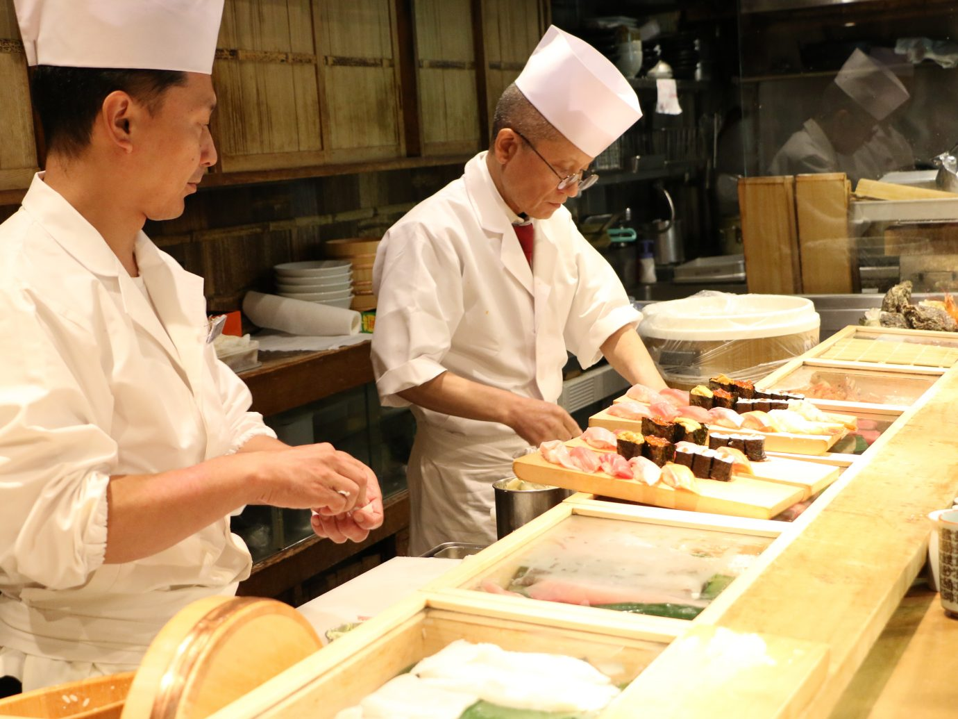 Sushi chefs preparing Sushi plate at small restaurant in Tsukiji Fish Market