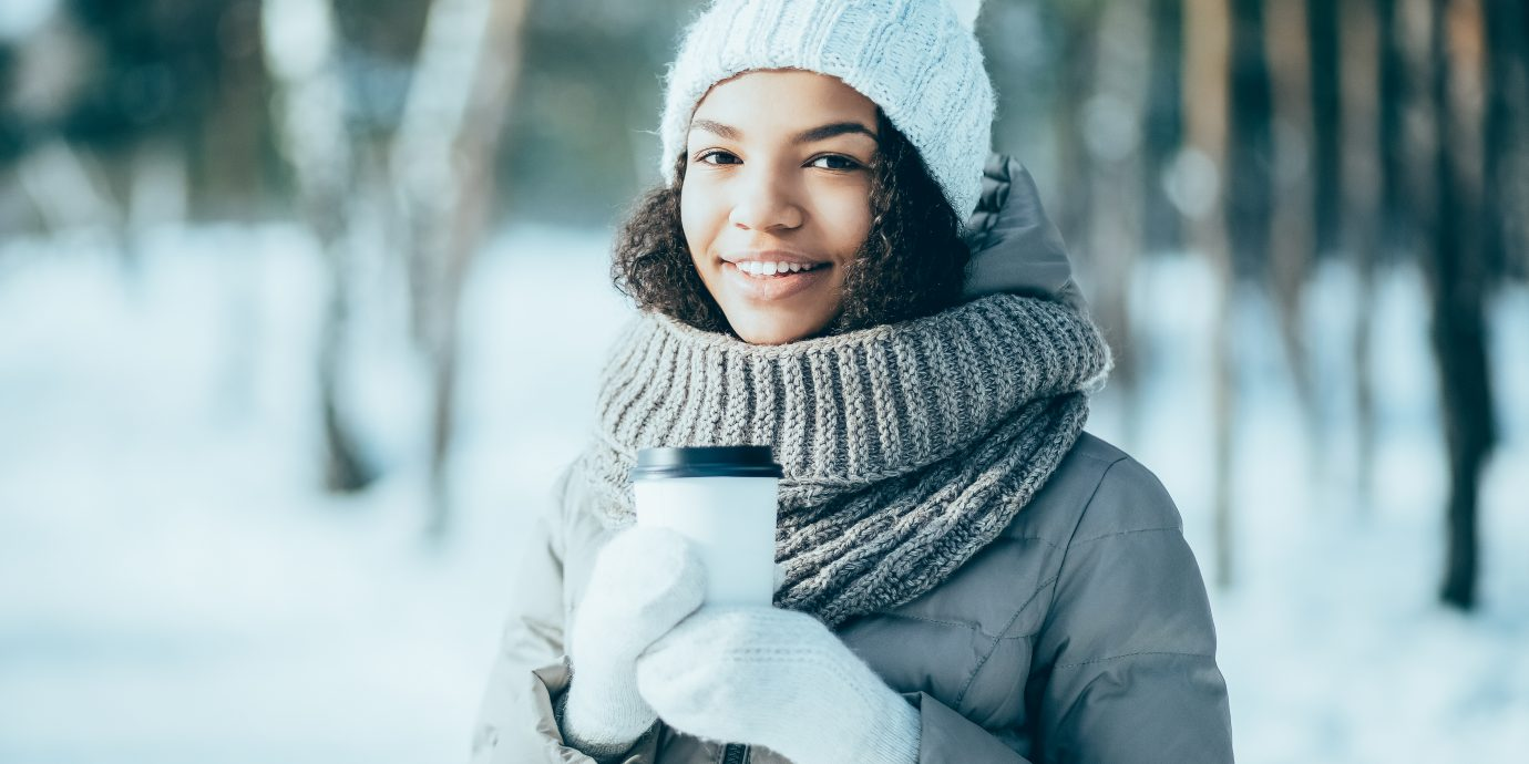 woman bundled up in coat, hat, mittens, and scarf, drinking coffee with snowy woods in the background