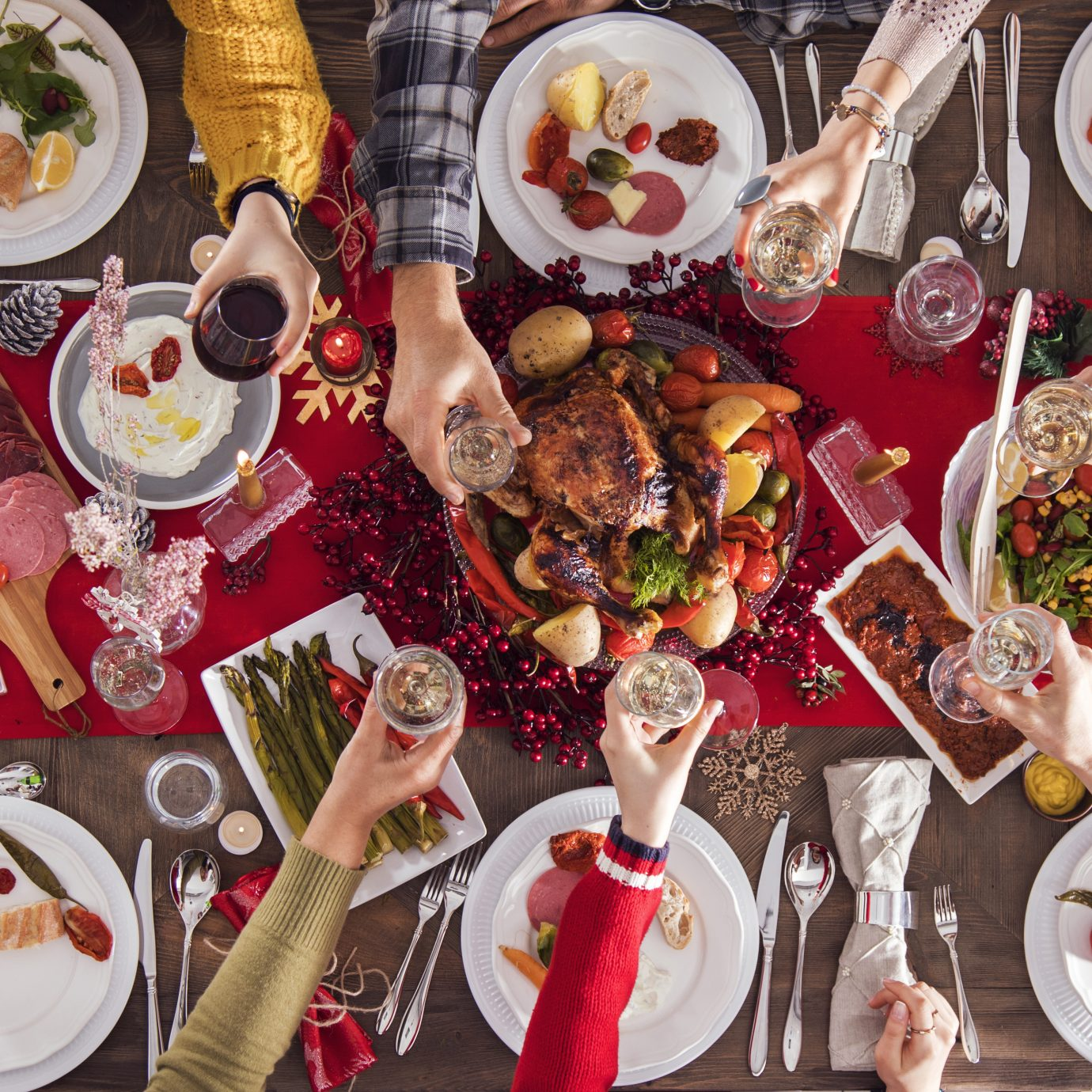 Christmas new year dinner group cheers with prepared food on table