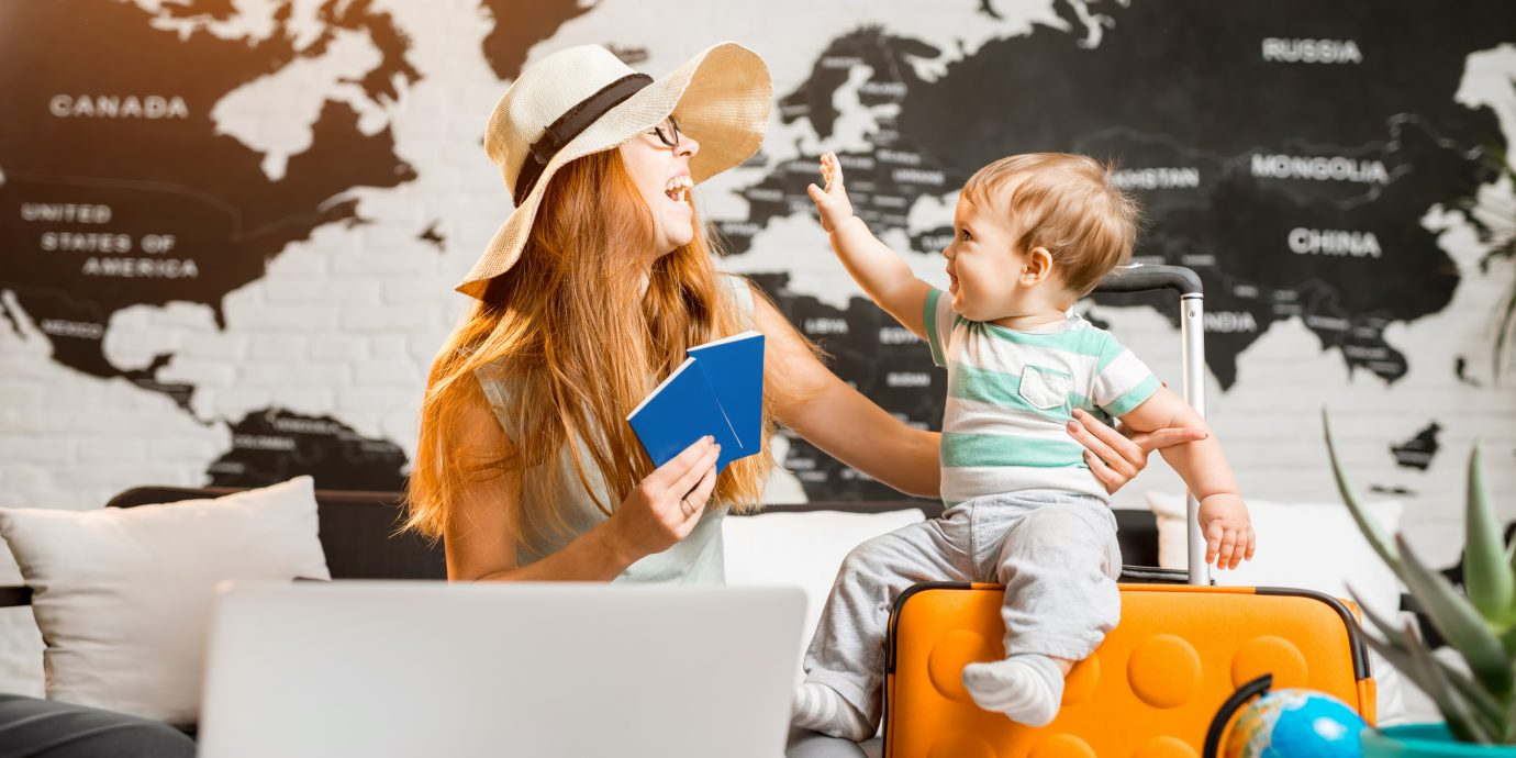 Happy and playful woman with baby boy sitting at the travel agency office with beautiful map on the background ready for a summer vacation