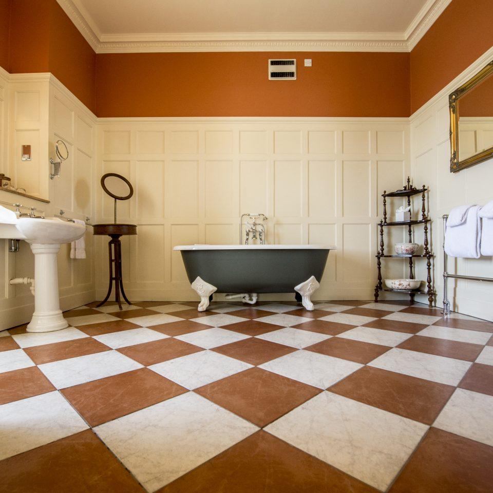 Dull orange bathroom with checkered orange/white flooring and large tub