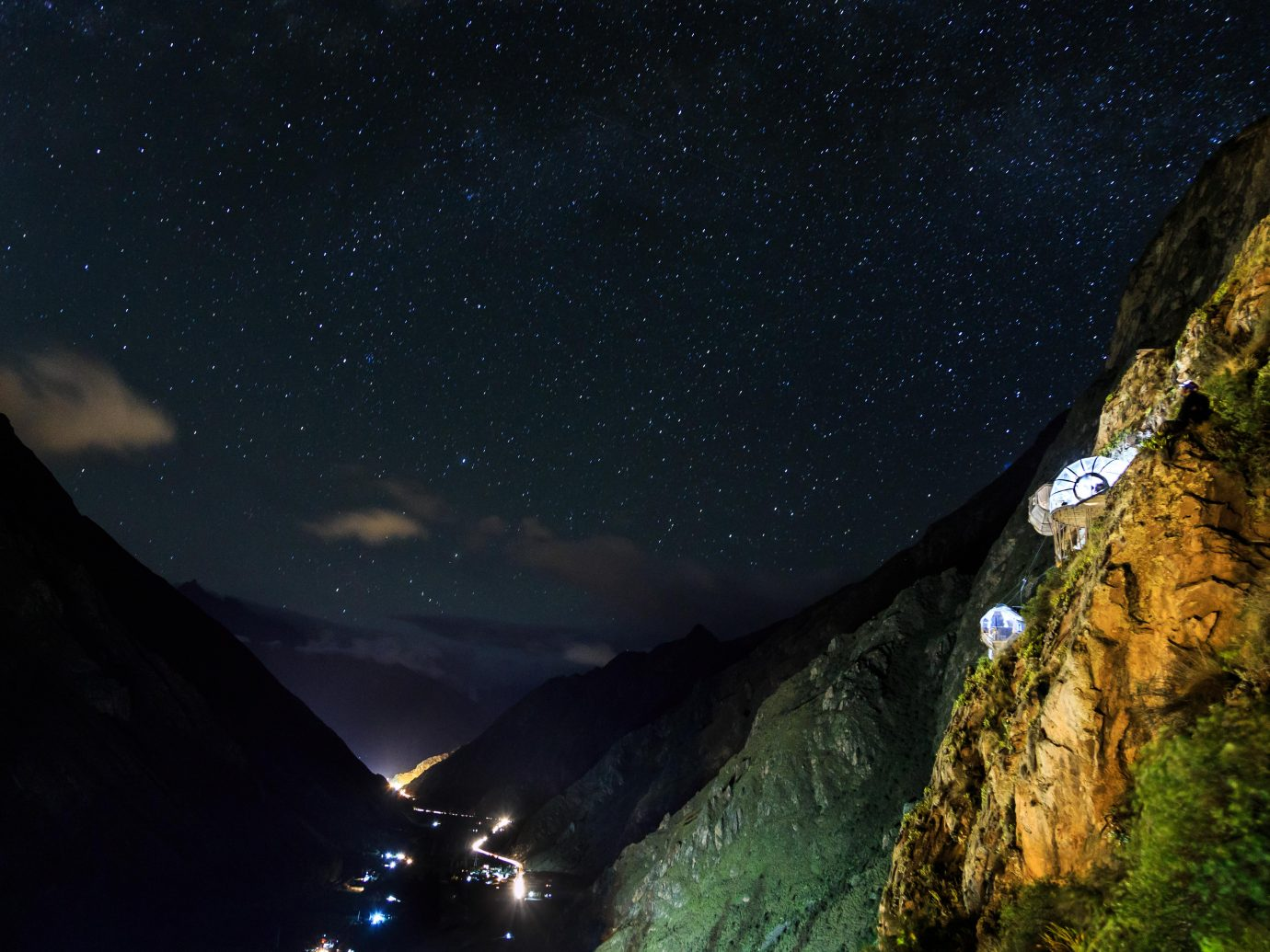 Room pods hanging on mountain sides with view of valley at night