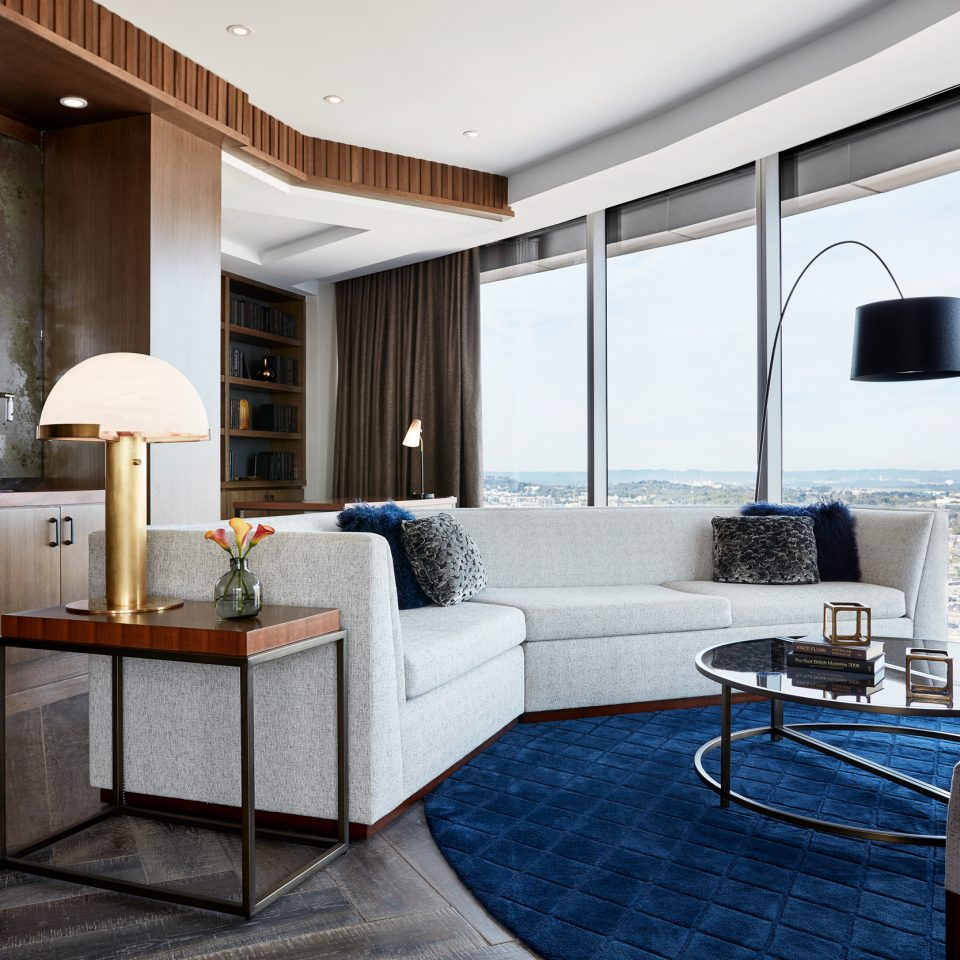 Presidential suite with white couch and blue rug