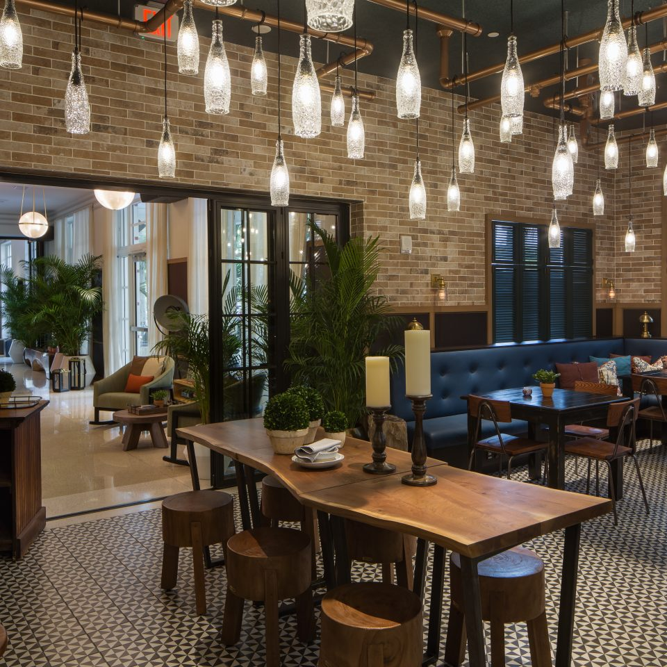 Restaurant with chunky wooden stools, beautiful glass hanging lights, royal blue booths