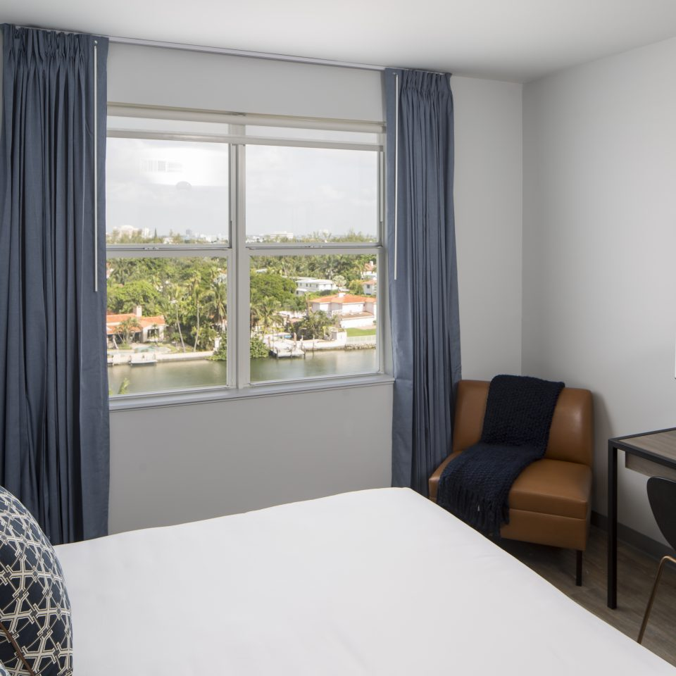 Room with large white bed with view of Miami outside