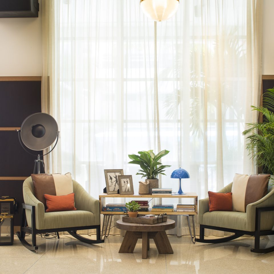 Lobby with two chairs, a large window with see through curtains, and house plants