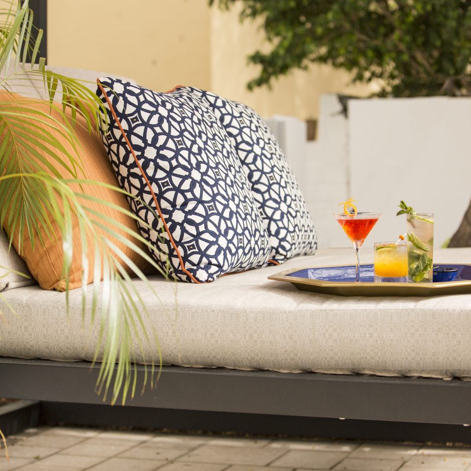 Outdoor deck furniture with cushions and a tray of three different alcoholic drinks