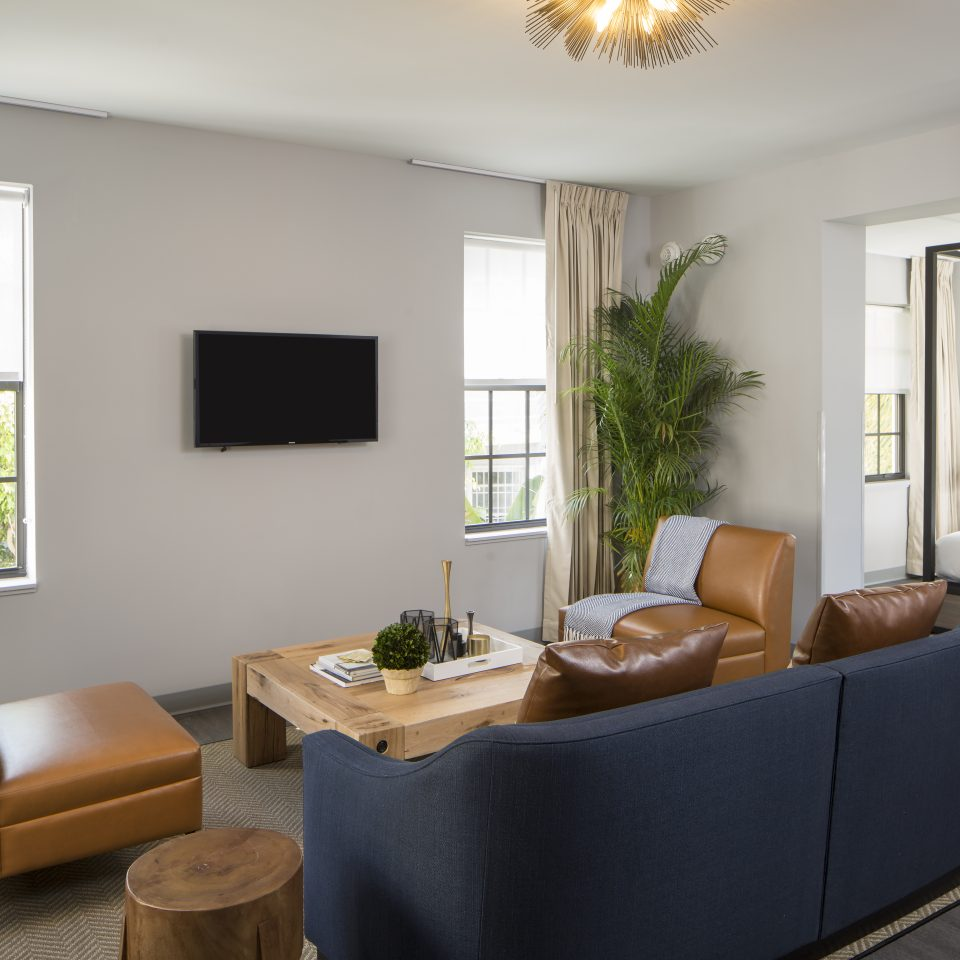Seating area facing television outside a room with a large bed