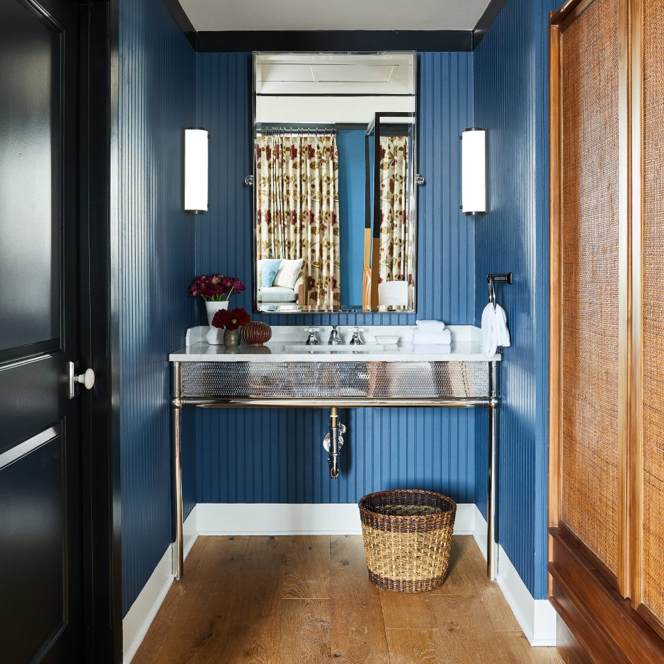 Blue triped wall room with hard wood floors and a sink with a mirror above it