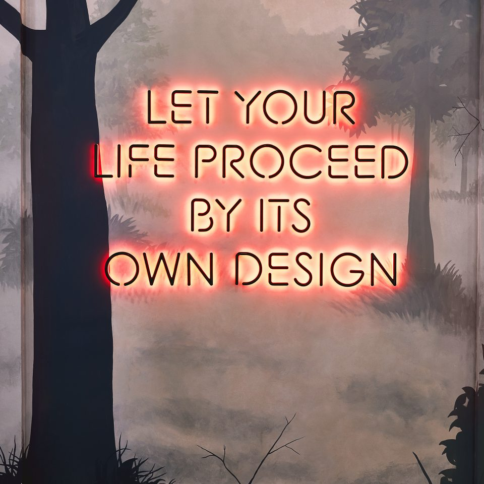 "Lit wall design saying ""Let your life proceed by its own design"""