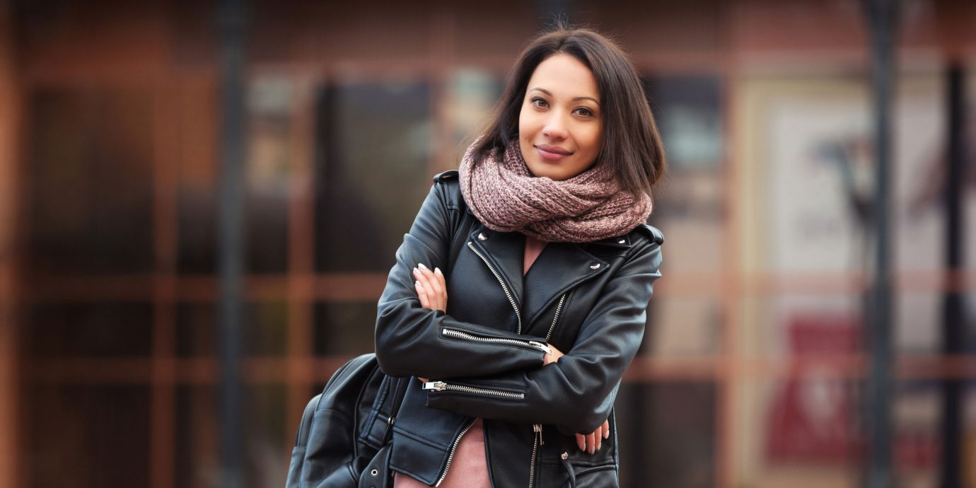 Young fashion woman with backpack walking in city street Stylish female model in black leather jacket outdoor