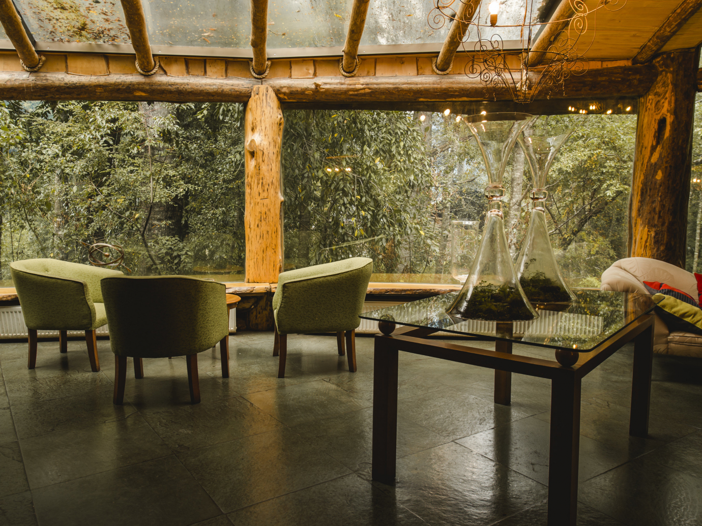 Interior seating space with wall sized windows showing the lush outdoors