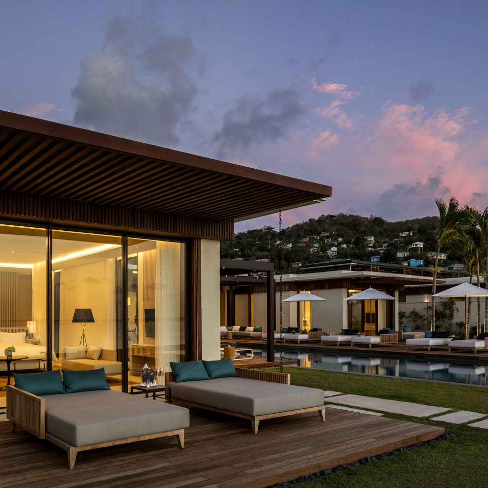 villa outdoor wooden patio with two day beds at dusk
