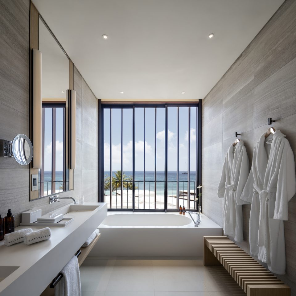 bathroom with tub next to window overlooking the beach