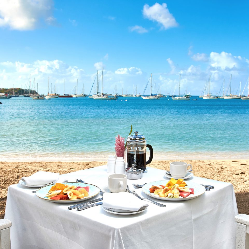set table with breakfasts and fruits on the beach looking over numerous sailboats in bright blue water