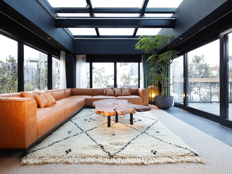 Living room area with long wrap around orange couch, open windows on ceilings and walls, and a fancy table