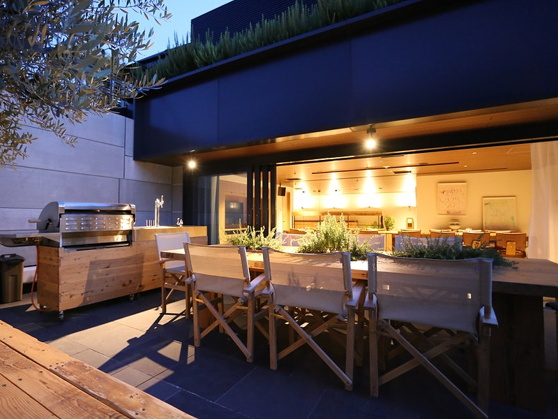 Outdoor patio area at dusk with a grill
