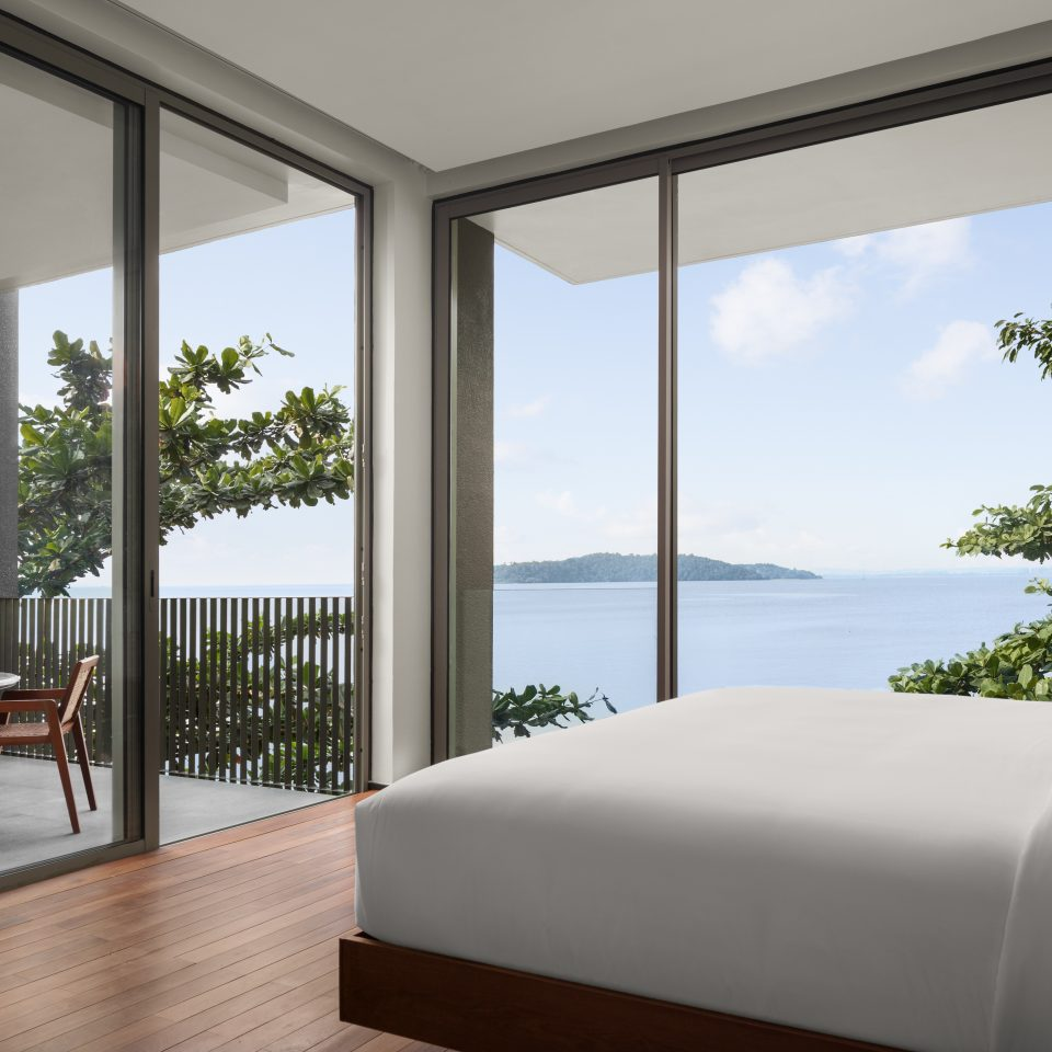bed with large wall windows that look over ocean with a balcony