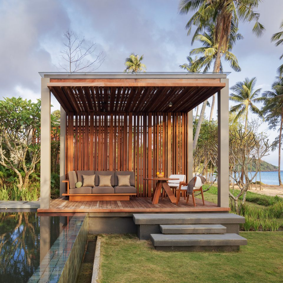 large wooden structure holding chairs, couches, and tables outdoors next to a pool