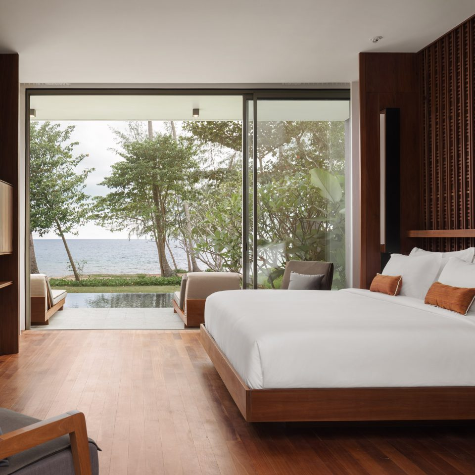 bed in a room with an open wall window overlooking both a pool and ocean