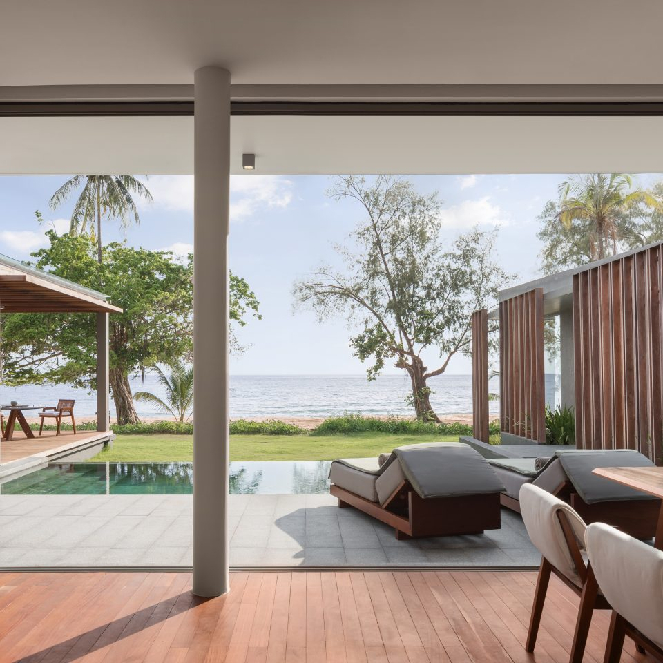 large windows in living room overlooking patio with pool, following grass and a beach