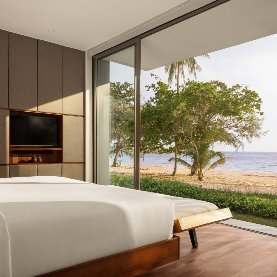 bed overlooking ocean with large windows