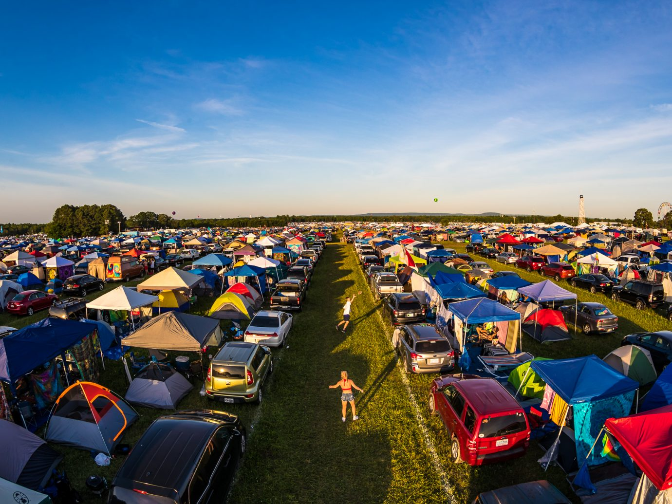 overhead shot of people playing games between a line of cars and tents