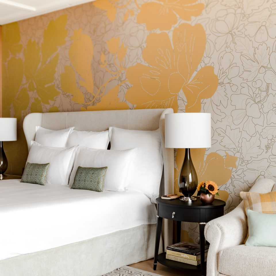suite with yellow walls and bed posts with lamps