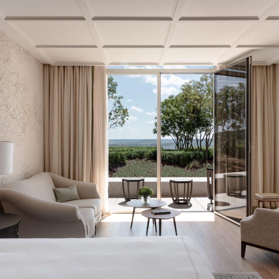 suite with large clear doors opening onto small balcony overlooking vineyard