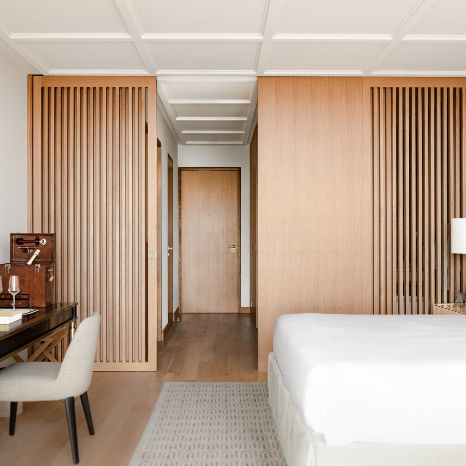 view of door to exit, bed, and desk in a suite with light wood accents