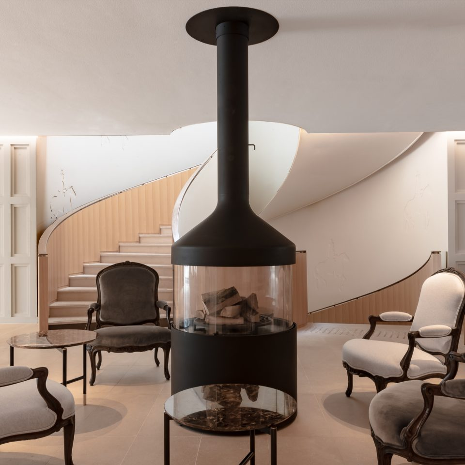 room with center fireplace and chairs around it and a spiral staircase in the background