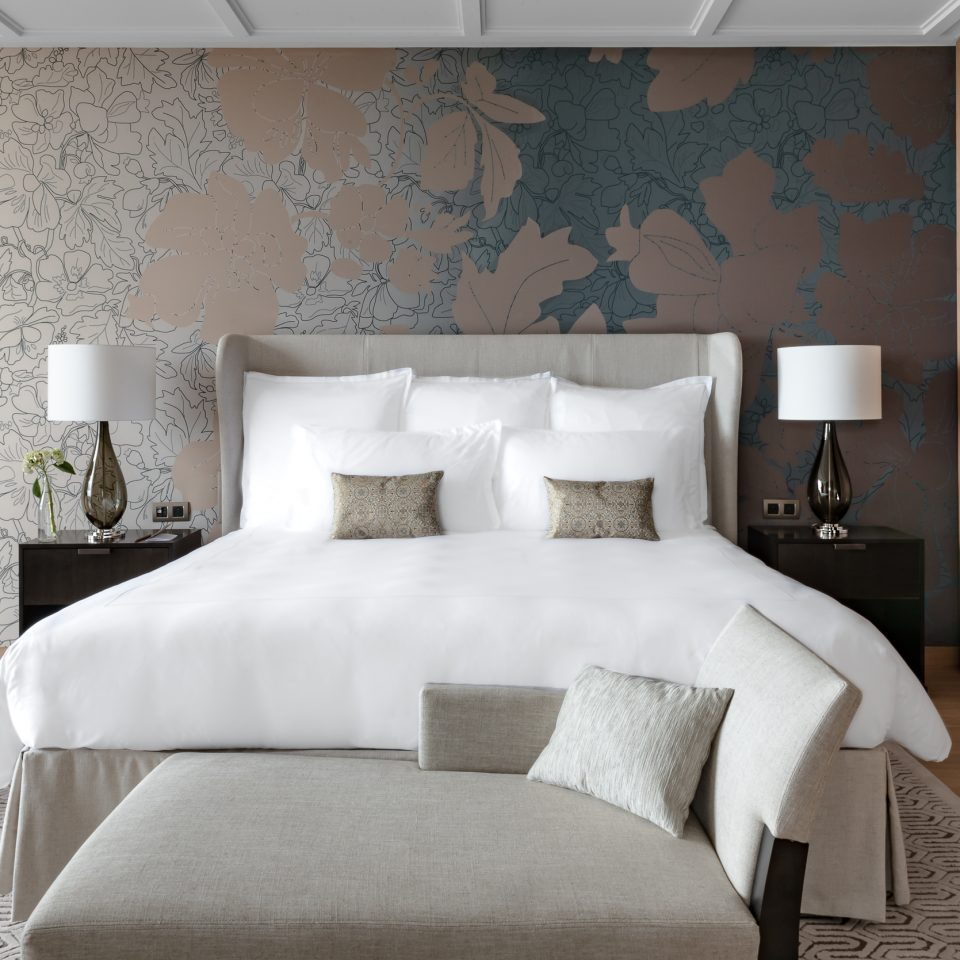 white large bed in a suite with floral grey, beige, and blue walls