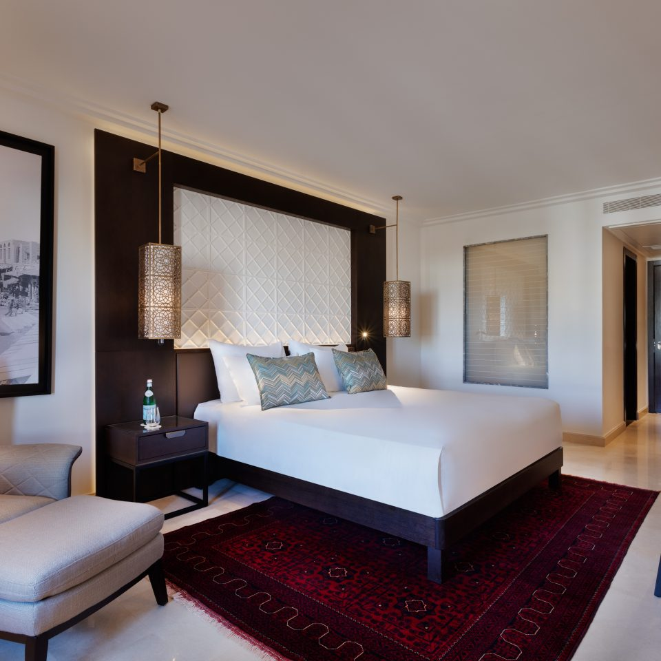 executive room with white bed and red space carpet