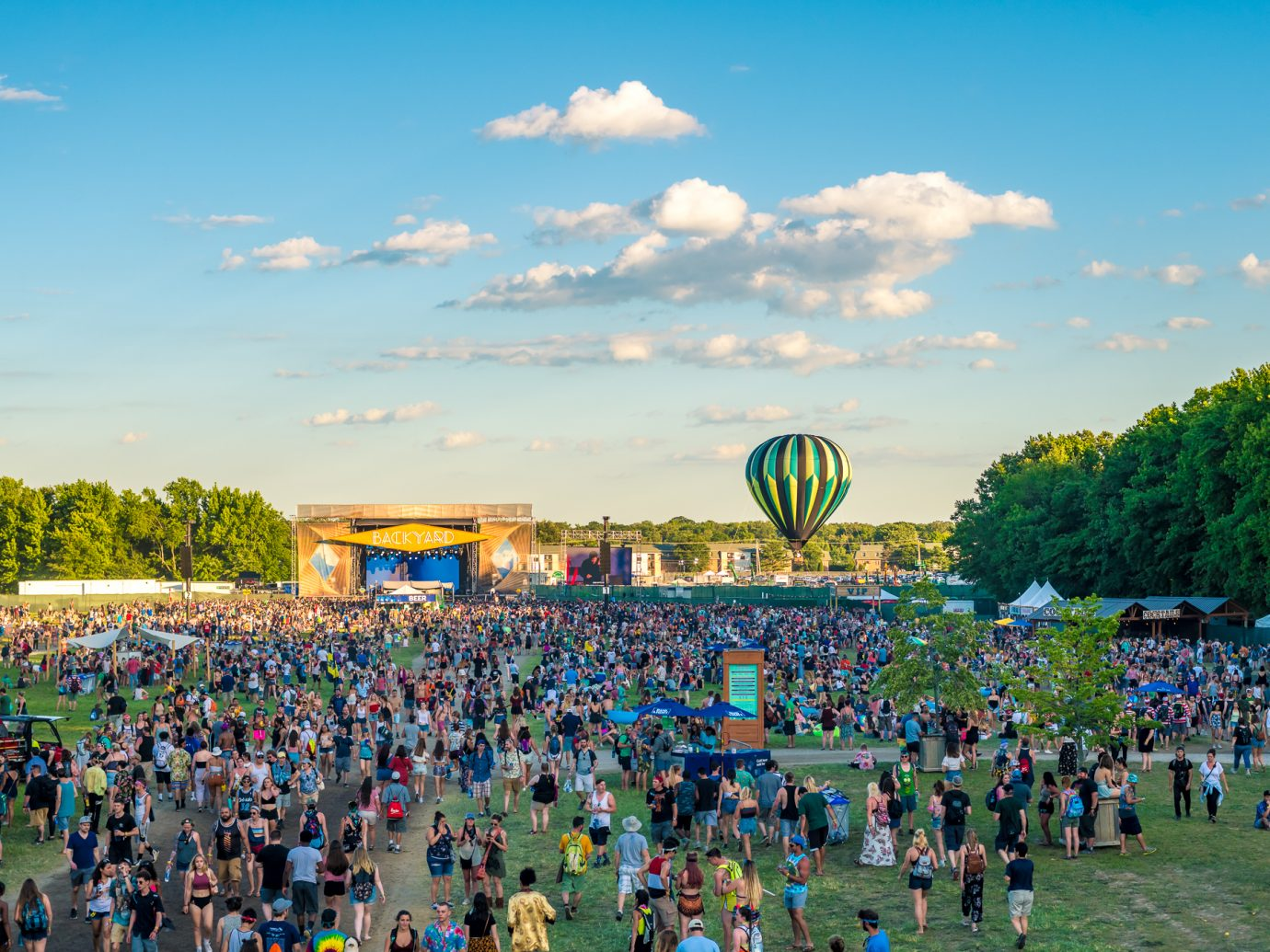 festivalgoers taken from overhead with views of sunny day, hot air balloon, and stage