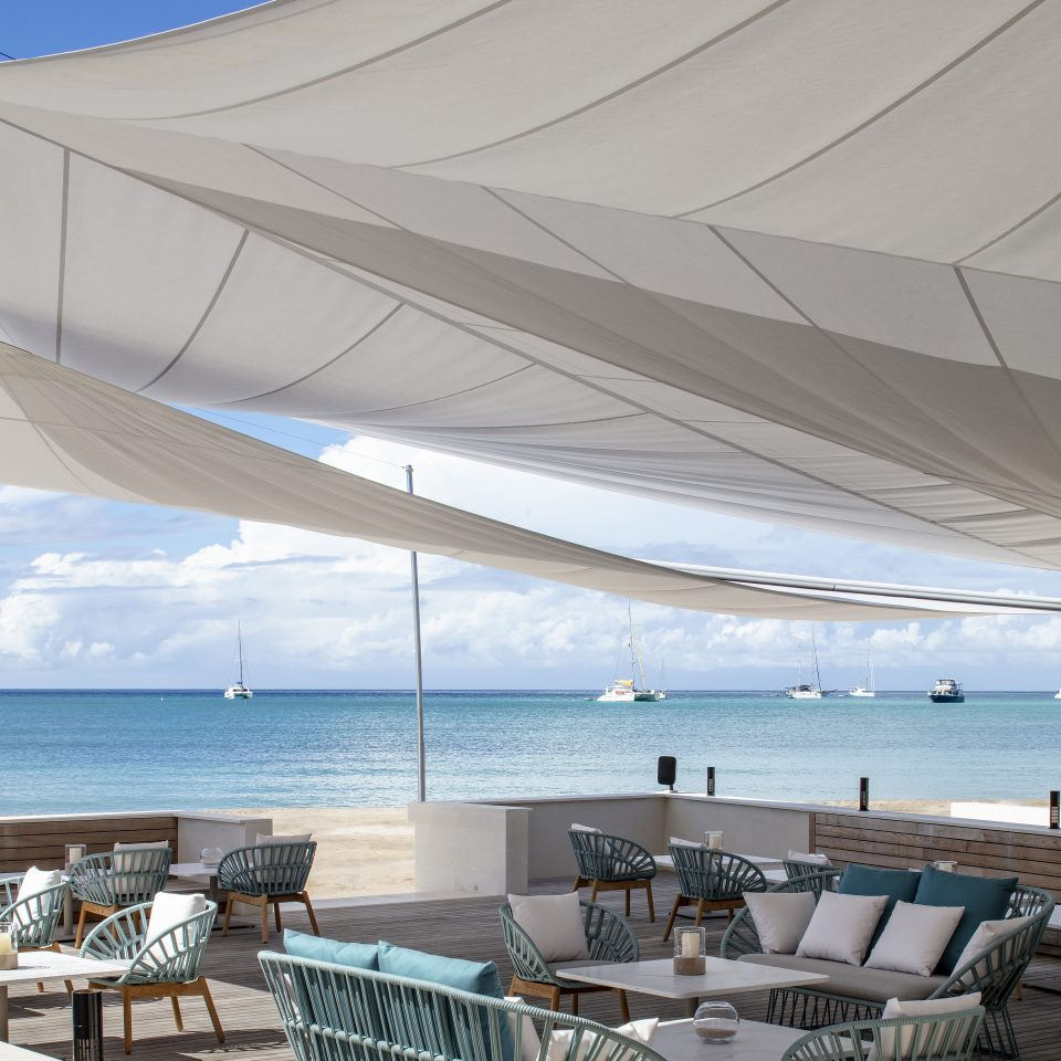 outdoor lounge area covered by white cloth overhead for shade overlooking white sands and blue waters