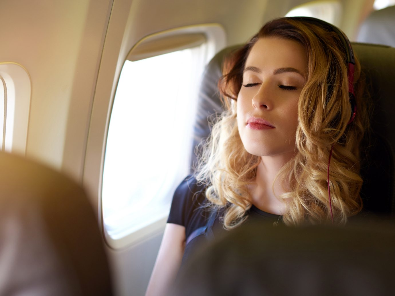 A young woman with her eyes closed enjoying a good and relaxing flight.photo taken in the airplane.
