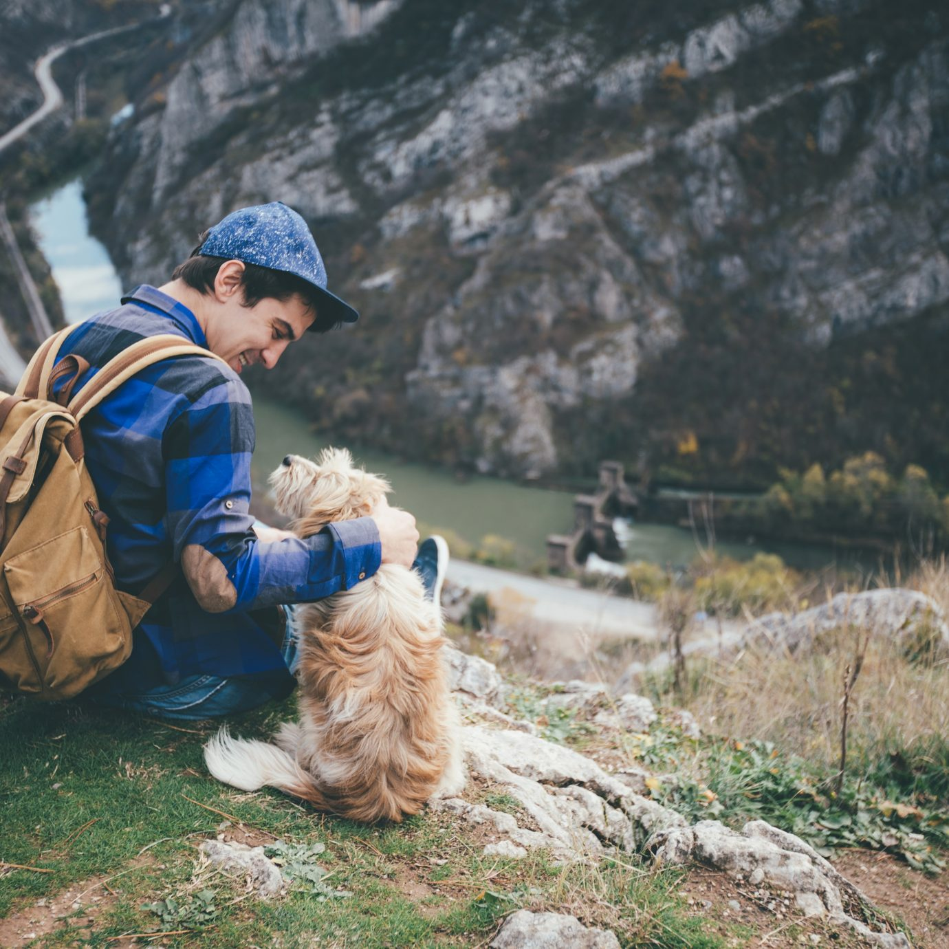 Young traveler with backpack petting dog on a mountain top