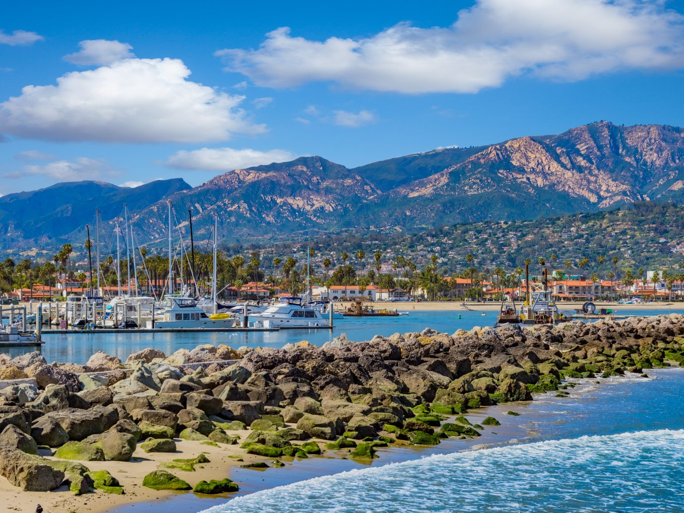 moored recreational boats; California marina scene; safe harbor; Southern California recreation; Santa Barbara Harbor, mountain range, leisure boats, water reflections, clear sky, still water, breakwater