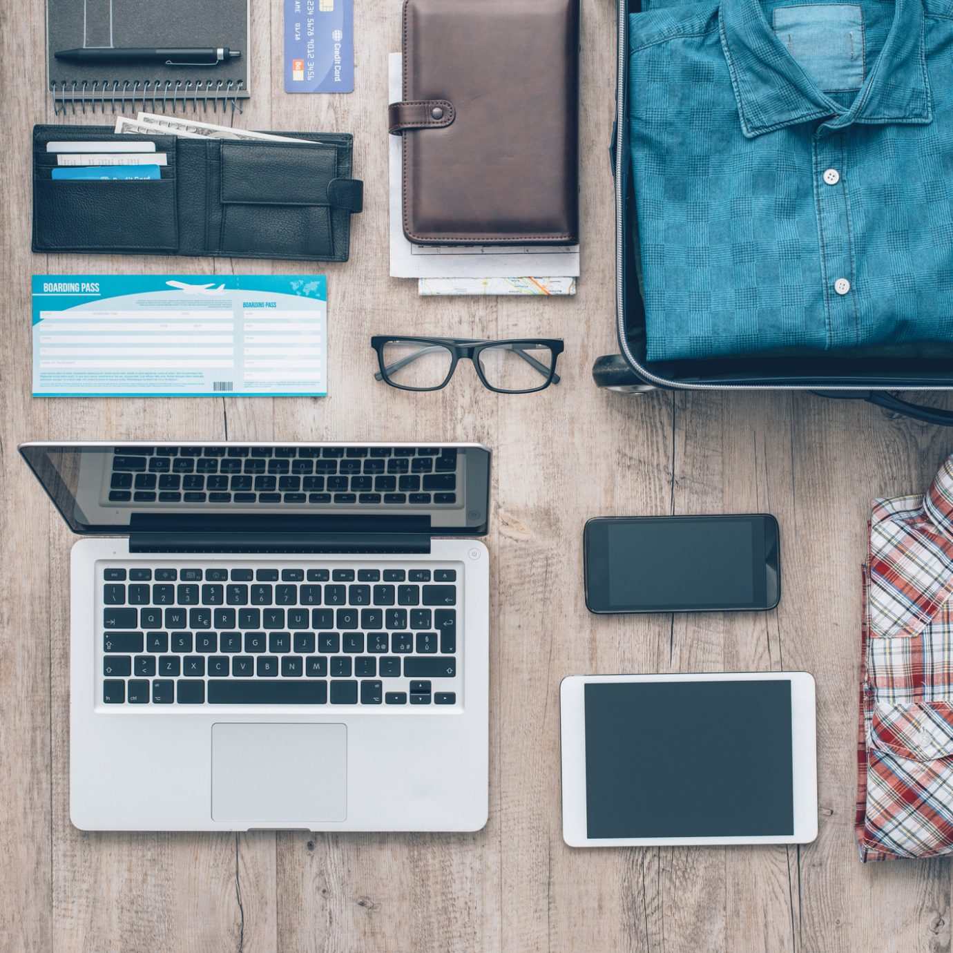 Travel equipment on a desktop: clothing, wallet, laptop, tablet, smartphone and personal accessories, travel and vacations concept