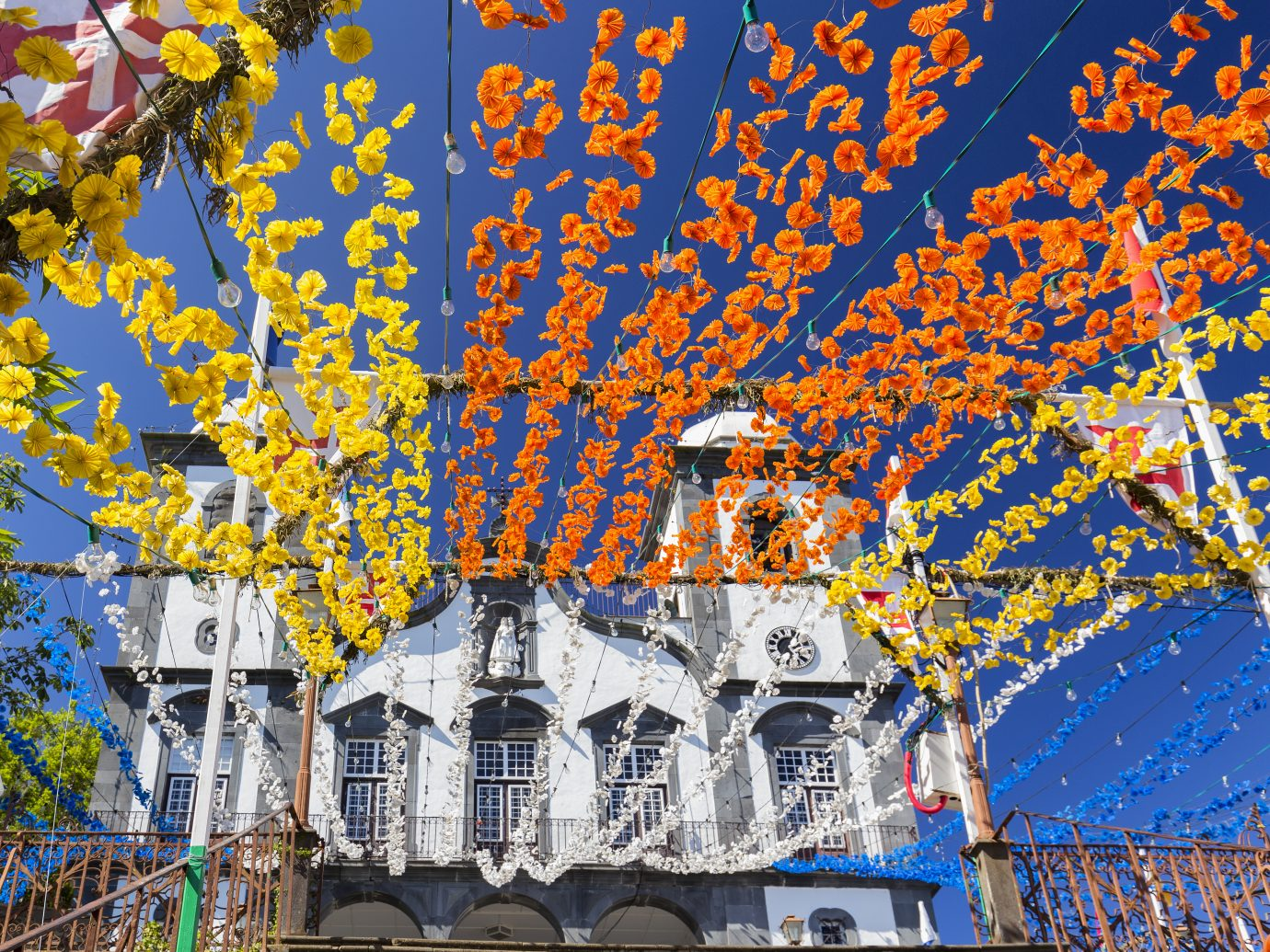 Decorate yellow, orange, blue and white flowers strung up leading to the Church of our Lady of Monte in Funchal, Portugal.