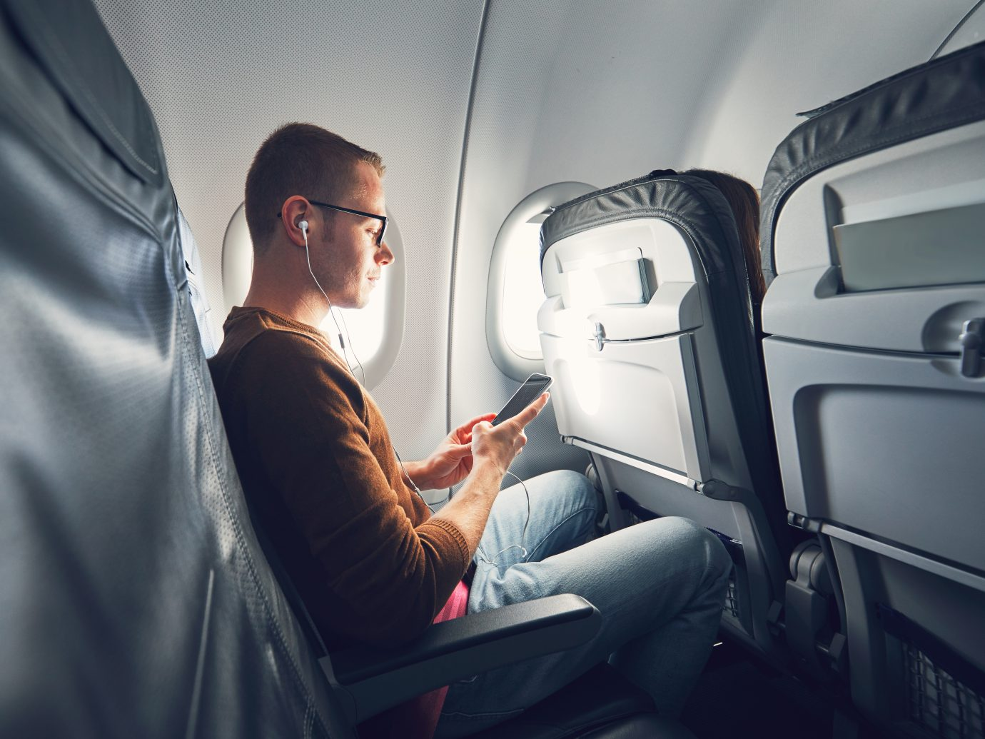 Young man (traveler) using smart phone during flight and listening music.