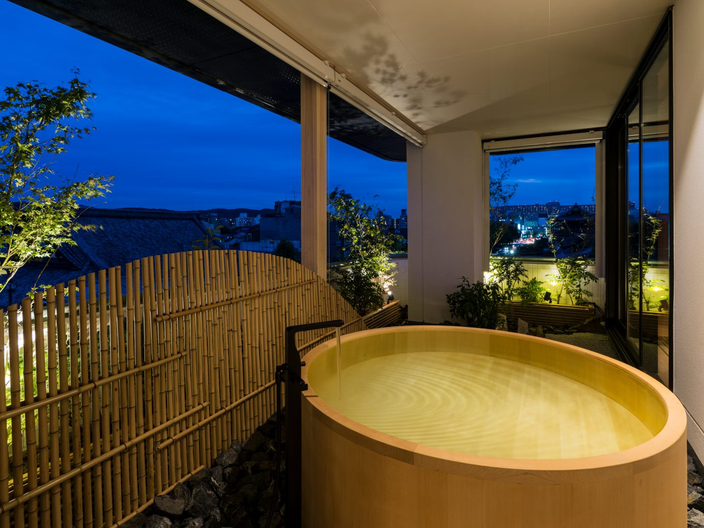 outdoor large wooden circle bathtub at night