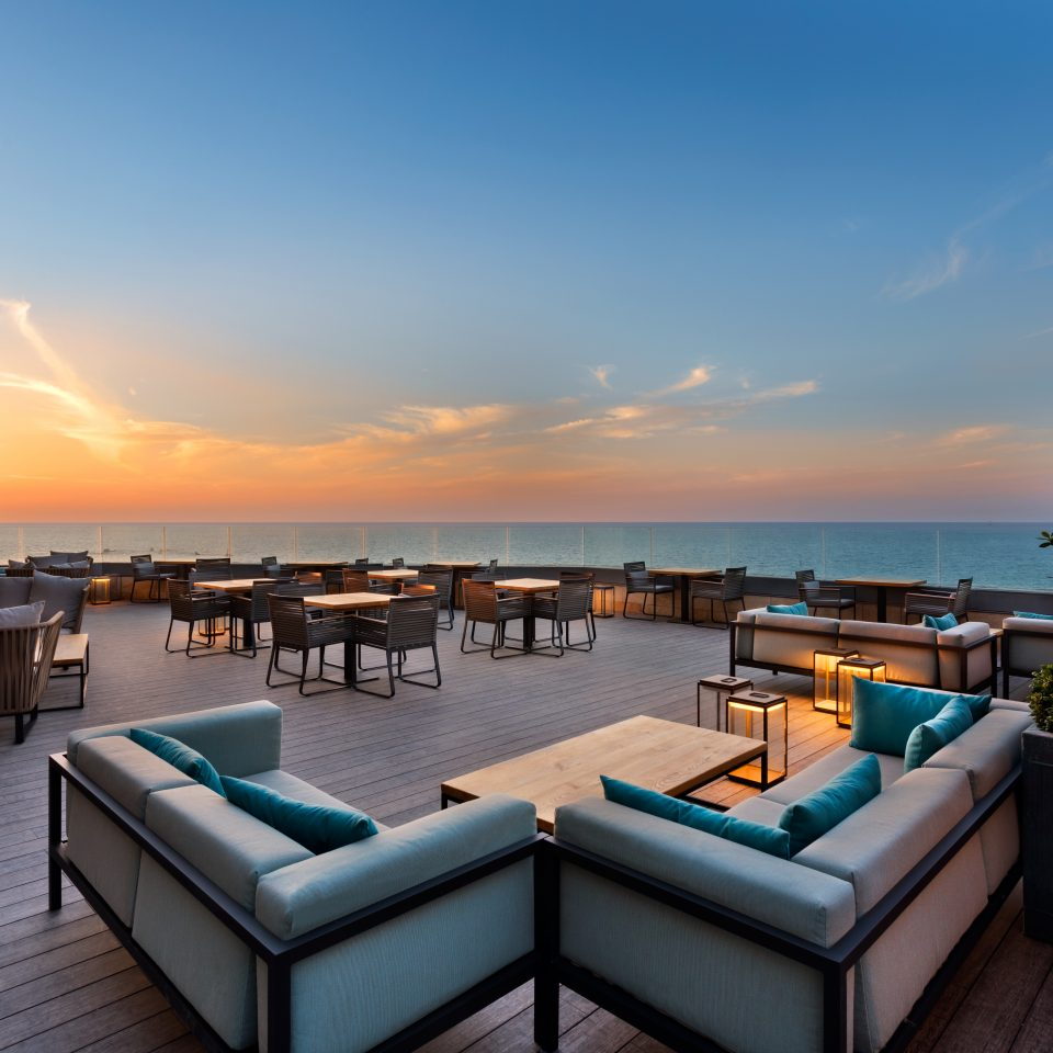 large hard wood outdoor patio space with numerous tables and couches at sunset with view of ocean