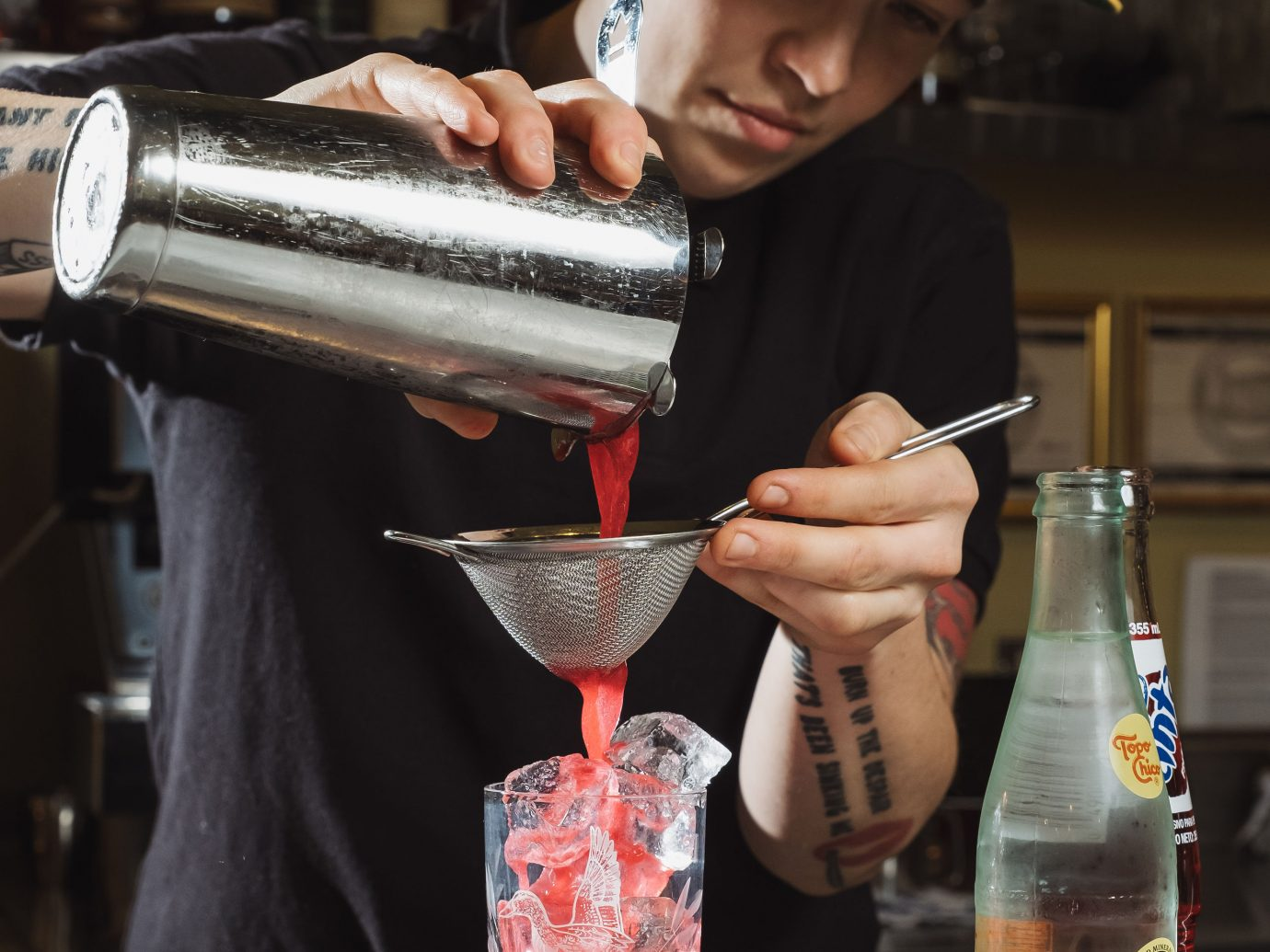 person with tattoos straining a drink