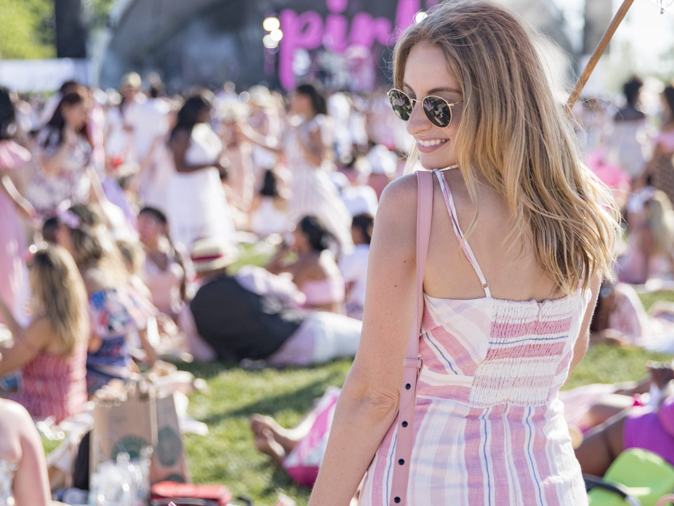 girl in pink and white dress enjoying herself in front of a stage at a music festival