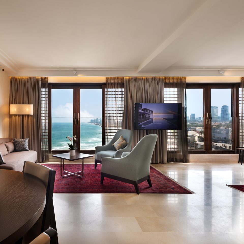premium suite with a round table holding wine and treats with large window views of the beach